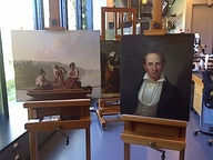 Two paintings on easels: George Caleb Bingham's Boatmen on the Missouri and Portrait of John A. Trigg